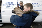 Dog owners wait outside a mobile veterinary clinic run by the Victoria Animal Hospital in Hackney, East London. The clinic helps those on low income as the treatment is provided for free or for a smal... - Rogan Macdonald - ,2000s,2007,adolescence,adolescent,adolescents,animal,Animal Welfare,animals,boy,boys,canine,canines,carries,carry,carrying,charitable,charities,charity,child,CHILDHOOD,children,cities,city,clinic,cli