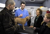 Vet, Mark Bossley, introduces some dog owners to a Blue Cross card, in a mobile veterinary clinic run by the Victoria Animal Hospital in Hackney, East London. The clinic helps those on low income as t... - Rogan Macdonald - 17-01-2007