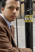 Ed Husain author of 'The Islamist', besides an islamist sticker advocating Sharia Law near the East London Mosque, Whitechapel - Rogan Macdonald - 13-04-2007