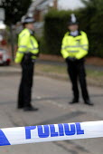 Police stand guard behind police tape at Walton Drive after a police raid (where arrests were made after a plot to blow up transatlantic flights was uncovered). In High Wycombe, Buckinghamshire, U.K. - Rogan Macdonald - 2000s,2006,adult,adults,area,areas,barrier,caution,cities,city,CLJ crime law justice,communities,community,communties,counterterrorism,Counter-terrorism,dangerous,force,guard,guarding,helmet,helmets,h