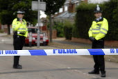 Police stand guard behind police tape at Walton Drive after a police raid (where arrests were made after a plot to blow up transatlantic flights was uncovered). In High Wycombe, Buckinghamshire, U.K. - Rogan Macdonald - 2000s,2006,adult,adults,area,areas,AUTO,AUTOMOBILE,AUTOMOBILES,AUTOMOTIVE,barrier,car,cars,caution,cities,city,CLJ crime law justice,communities,community,communties,counterterrorism,Counter-terrorism