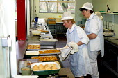 Dinner lady serving up hot food, School canteen. - Roy Peters - 20-01-2003