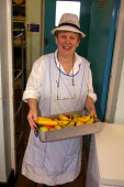 Dinner lady serving up fresh fruit, School canteen. - Roy Peters - 20-01-2003