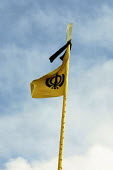 Gurdwara Sri Singh Sabha, Southall July 03The flag This is main Sikh symbol. The flag is called Nishan Sahib. On the outside are two swords which represent both the spiritual and temporal powers. Toge... - Roy Peters - 2000s,2003,alata,ASIAN,ASIANS,BAME,BAMEs,Black,BME,bmes,diversity,ethnic,ethnicity,flag,FLAGS,God,Gurdwara,Gurdwara Sri Singh Sabha temple,holy,Indian,minorities,minority,outside,people,poc,RELIGION,r