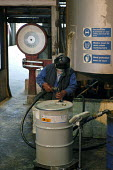 A worker pumps out a solution of tributyltin naphthenate in white spirit from a 200 litre drum into a vat of kerosene in the manufacture of pesticides, Newcastle upon Tyne. - Ray Smith - 16-05-2003
