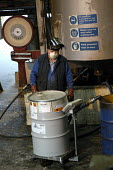 A worker tips 25 kg bags of resin nto a vessel of kerosene during the manufacture of pesticide based on tributyltin naphthenate and permethrin, Newcastle upon Tyne. - Ray Smith - 16-05-2003