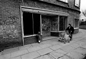 Mother and children walking past boarded-up shops & homes, Benchill, Manchester - Stefano Cagnoni - ,1980s,1988,bought,buy,buyer,buyers,buying,child,CHILDHOOD,CHILDREN,commodities,commodity,consumer,consumers,customer,customers,depression,DOWNTURN,female,goods,housing,juvenile,juveniles,kid,kids,Man