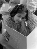 Child studying at Church of England primary school Nelson Lancashire 25.3.88 - Stefano Cagnoni - 1980s,1988,asian,BAME,BAMEs,black,BME,bmes,Church,churches,diversity,EDU education,ethnic,ethnicity,female,females,girl,GIRLS,LEARNING,minorities,minority,people,person,persons,poc,READ,reading,READS,