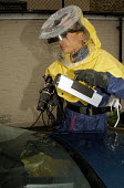 Police photographer from forensic laboratory using a Scenescope camera and UVC light source to examine and photograph finger prints on car. The American made Scenescope is the only one of its kind on... - Stefano Cagnoni - 06-10-1998