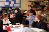 Teacher explaining conversion principles to Year 5 pupils during maths lessons at north London primary school. A primary support helper is working with a child in the background - Stefano Cagnoni - 04-02-1999