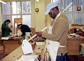 Student in the carpentry workshop at the College of North East London (CoNEL) - Stefano Cagnoni - 2000,2000s,BAME,BAMEs,black,BME,bmes,carpenter,carpenters,cities,city,College,colleges,diversity,EDU education,ethnic,ethnicity,FE,Further Education,Further Education,London,manual,minorities,minority
