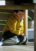 School boy excluded from mainstream school and now in Primary Pupil Referral Unit (PPRU), refusing to obey teaching staff by hiding below a climbing frame. The boy's face has been masked to protect hi... - Stefano Cagnoni - 15-03-2000