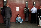 Homeless man begging as all around him people queue to withdraw cash from automatic cash machines - Stefano Cagnoni - 30-06-2000