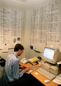 MAFF vet files potential further outbreaks of foot and mouth disease as they are telephoned through to the MAFF Emergency Control Centre in Westminster.The lists on the walls behind him are the cases... - Stefano Cagnoni - 28-03-2001