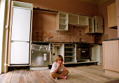 Despondent young child sitting in kitchen not finished to schedule by fitters - Stefano Cagnoni - 24-03-2002