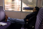 Passenger ignoring sign urging passengers not to put their feet on the train seats - Stefano Cagnoni - 29-10-2002