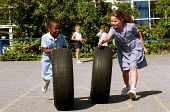 Girls having fun with some tyres during playtime at a Church of England primary school - Stefano Cagnoni - 2000s,2002,BAME,BAMEs,black,BME,bmes,child,CHILDHOOD,children,Church,churches,cities,city,cultural,diversity,EDU education,EMOTION,EMOTIONAL,EMOTIONS,ethnic,ethnicity,exercise,exercises,female,females