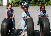 Girls having fun with some tyres during playtime at a Church of England primary school - Stefano Cagnoni - ,2000s,2002,appealing,BAME,BAMEs,black,BME,bmes,charming,child,CHILDHOOD,children,Church,churches,cities,city,cultural,cute,diversity,EDU education,EMOTION,EMOTIONAL,EMOTIONS,ethnic,ethnicity,exercise