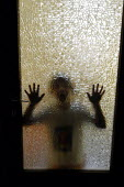 Child leaning against glass door having locked herself in the bathroom - Stefano Cagnoni - 22-08-2003