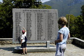 Boy watched by his younger sister reads the names on a commemorative memorial of hundreds of innocent civilians massacred during World War II by the Nazis at St Anna di Stazzema in Tuscany - Stefano Cagnoni - 2000s,2003,2nd,boy,BOYS,child,CHILDHOOD,children,COMMEMORATE,commemorating,commemoration,COMMEMORATIONS,commemorative,educating,education,eu,Europe,european,europeans,eurozone,families,family,hill,hil