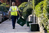 Worker collecting containers as part of recyclng scheme operated by Haringey Council - Stefano Cagnoni - 2000s,2003,authority,BAME,BAMEs,black,BME,bmes,c,carries,carry,carrying,cities,city,collect,collecting,collection,CONTAINER,containers,Council,Council Services,Council Services,diversity,domestic,door