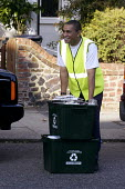 Worker collecting containers,recycling scheme operated by Haringey Council - Stefano Cagnoni - 2000s,2003,authority,BAME,BAMEs,black,BME,BME black,bmes,carries,carry,carrying,cities,city,collect,collecting,collection,CONTAINER,containers,council,council services,council services,diversity,door