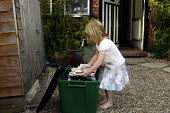 Child playing household waste into a container as part of recyclng scheme operated by Haringey Council - Stefano Cagnoni - 2000s,2003,authority,c,carries,carry,carrying,child,CHILDHOOD,children,cities,city,collect,collecting,collection,Council,Council Services,Council Services,domestic,door,ENI environmental issues,enviro