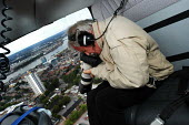 Yann Arthus-Bertrand, photographer of the 'earth from the air' series at work on a helicopter above London - Stefano Cagnoni - 05-07-2004