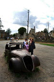 Tourists examine the remnants of a car in Oradour-sur-Glane, a town in France left in ruins to commemorate the Nazi massacre that took place there during the Second World War - Stefano Cagnoni - 2,2000s,2004,ace culture WW2,attraction,Burnt Out,death,deaths,DESTROYED,destruction,devastation,died,EDU education,eu,Europe,european,europeans,eurozone,FACISM,FACIST,FACISTS,families,family,FAR RIGH