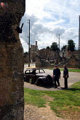 Tourists filter quietly through Oradour-sur-Glane, a town in France left in ruins to commemorate the Nazi massacre that took place there during the Second World War - Stefano Cagnoni - 2,2000s,2004,ace culture WW2,attraction,AUTO,AUTOMOBILE,AUTOMOBILES,AUTOMOTIVE,Burnt Out,car,CARS,death,deaths,DESTROYED,destruction,devastation,died,EDU education,eu,Europe,european,europeans,eurozon