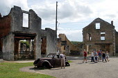 Tourists filter quietly through Oradour-sur-Glane, a town in France left in ruins to commemorate the Nazi massacre that took place there during the Second World War - Stefano Cagnoni - 2,2000s,2004,ace culture WW2,attraction,AUTO,AUTOMOBILE,AUTOMOBILES,AUTOMOTIVE,Burnt Out,car,CARS,CHILD,CHILDHOOD,children,crowds,death,deaths,DESTROYED,destruction,devastation,died,EDU education,eu,E