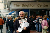 Political activist selling a copy of the Communist Party's daily newspaper, The Morning Star, outside the Brighton conference centre - Stefano Cagnoni - 2000s,2004,alternative,campaign,campaigning,CAMPAIGNS,communism,Communist,Communists,conference,conferences,leaflet,leafleting,LEAFLETS,LEAFLETTING,left,left wing,leftwing,media,Morning,news,newspaper