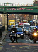 Its Global Warming Stoopid graffiti on a railway bridge above a queue of traffic on a major arterial route streaming into London during the extended rush hour on a Monday morning - Stefano Cagnoni - 07-02-2005