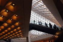 Visitors entering the Louvre Museum via the escalators beneath its Pyramid entrance - Stefano Cagnoni - 2000s,2005,ACE,ACE arts culture,ace culture,architecture,Art Gallery,arts,attraction,buildings,culture,design,down,entrance,Escalator,Escalators,eu,Europe,european,europeans,exhibition,French,futurist