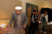 Elderly French voter casts his ballot in the Town Hall polling station of Le Blanc Mesnil, a northern suburb of Paris, in the national referendum on the European Constitution, as the younger generatio... - Stefano Cagnoni - 29-05-2005