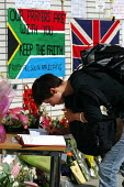 Visitors sign a book of condolences at a makeshift shrine outside King's Cross Station, one of the sites of the terrorist attacks which caused death and injury to many Londoners - Stefano Cagnoni - 12-07-2005