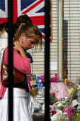 Young woman reads tributes to the victims of the terrorist bombings at a makeshift shrine outside King's Cross Station, one of the sites of the terrorist attacks which caused death and injury to many... - Stefano Cagnoni - 12-07-2005