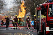Firefighters drawing the hoses from their engine to tackle a blaze casued by a JCB fracturing a gas pipe whilst digging the road - Stefano Cagnoni - 30-01-2005