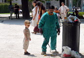 Young boy watching as street cleaner picks up litter strewn in a park - Stefano Cagnoni - 28-05-2005