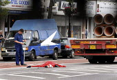 Police Officer takes measurements at the scene of a road fatality on Holloway Road in north London. The victim ws killed as he crossed this busy arterial route by the HGV seen in the background - Stefano Cagnoni - 13-07-2006