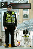 Dog handler with the Metropolitan Police Search Dog Section on duty at a Docklands Light Railway station - Stefano Cagnoni - 2000s,2008,adult,adults,animal,animals,canine,CLJ,DLR,Dog,dogs,force,handler,handlers,lead,looking,MATURE,MET,Officer,officers,platform,PLATFORMS,Police,policeman,policemen,policing,RAIL,railway,RAILW