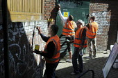 Offenders wearing tabards with Community Payback on their backs clean up graffiti on walls in East London - Stefano Cagnoni - 2000s,2009,against,anti,anti social behavior,anti social behaviour,anti socialanti social behavior,antisocial,antisocial behaviour,antisocialvandalise,antisocialvandalize,behavior,behaviour,by hand,cl