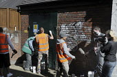 Offenders wearing tabards with Community Payback on their backs being filmed by a news tv crew as they clean up graffiti on walls in East London - Stefano Cagnoni - 09-06-2009