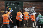 Offenders wearing tabards with Community Payback on their backs clean up graffiti on walls in East London overseen by their supervisor in the green tabard - Stefano Cagnoni - 09-06-2009