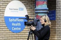 Woman Camera Operator filming outside Spitalfields Health Centre in East London. - Stefano Cagnoni - 19-06-2009