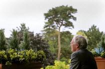 Older man contemplating the scene in front of him - Stefano Cagnoni - 2000s,2009,contemplating,contemplation,depressed,depression,disturbed,enjoy,enjoying,ENJOYMENT,foliage,future,garden,gardens,grey,hair,haired,intelligence,intelligent,leaves,Leisure,LFL,LFL lifestyle