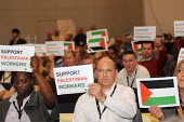 Delegates from the FBU hold up posters in support of Palestinian workers during a debate on a motion calling for a boycott of Israeli goods at the 2009 TUC in Liverpool - Stefano Cagnoni - 17-09-2009