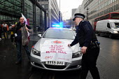 Police officer called to prevent post office workers blocking the road outside the Department for Business in protest at Government plans to privatise Royal Mail and the Post Office removes CWU poster... - Stefano Cagnoni - 2010,2010s,activist,activists,adult,adults,blocking,Business,CAMPAIGN,campaigner,campaigners,CAMPAIGNING,CAMPAIGNS,CLJ,CWU,demonstrate,DEMONSTRATING,demonstration,DEMONSTRATIONS,Department,force,Gover