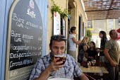 Customer drinking a glass of Leffe Beer at a table at a cafe in Arles in southern France. - Stefano Cagnoni - 06-08-2011