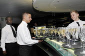 Catering workers at a champagne bar in the central London. - Stefano Cagnoni - 2010s,2011,alcohol,BAME,BAMEs,bar,Bar staff,bar tending,BARS,Bartender,bartenders,bartending,black,BME,bmes,cater,caterer,caterers,catering,champagne,CHAMPAIGN,cities,city,cultural,diversity,drink,dri